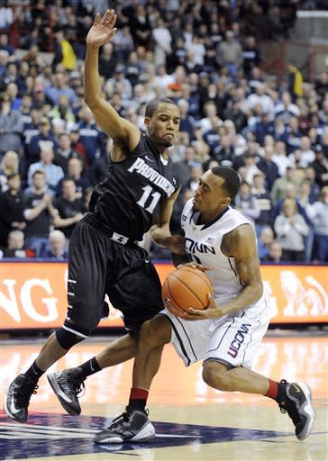 Connecticut's Ryan Boatright, right, is fouled by Providence's Bryce Cotton late in overtime of Connecticut's 63-59 win in an NCAA college basketball game in Storrs, Conn., Saturday, March 9, 2013. (AP Photo/Fred Beckham)