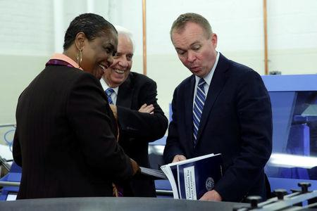 Office of Management and Budget (OMB) Director Mick Mulvaney (R) reacts next to Government Publishing Office Director Davita Vance-Cooks (L) as they inspect the FY2018 budget production run in Washington, U.S., May 19, 2017. REUTERS/Yuri Gripas