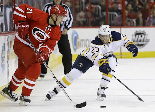 Carolina Hurricanes' Drayson Bowman (21) and Buffalo Sabres' Ville Leino (23), of Finland, skate for possession of the puck during the first period of an NHL preseason hockey game on Friday, Sept. 27, 2013, in Raleigh, N.C.. (AP Photo/Gerry Broome)