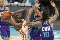 Atlanta Hawks center Clint Capela (15) looks to pass as he drives into Charlotte Hornets forward Miles Bridges during the first half of an NBA basketball game in Charlotte, N.C., Sunday, April 11, 2021. (AP Photo/Nell Redmond)