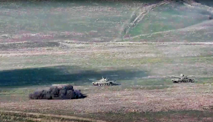 In this image taken from a footage released by Armenian Defense Ministry on Sunday, Sept. 27, 2020, Armenian army destroys Azerbaijani tanks at the contact line of the self-proclaimed Republic of Nagorno-Karabakh, Azerbaijan. Fighting between Armenia and Azerbaijan has broken out around the separatist region of Nagorno-Karabakh and the Armenian Defense Ministry says two Azerbaijani helicopters have been shot down. Ministry spokeswoman Shushan Stepanyan also said Armenian forces hit three Azerbaijani tanks. (Armenian Defense Ministry via AP)
