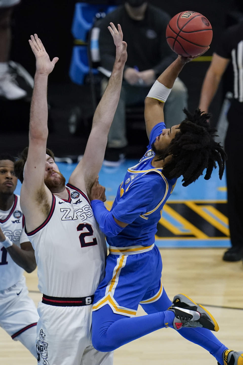 UCLA guard Tyger Campbell, right, shoots over Gonzaga forward Drew Timme (2) during the first half of a men's Final Four NCAA college basketball tournament semifinal game, Saturday, April 3, 2021, at Lucas Oil Stadium in Indianapolis. (AP Photo/Michael Conroy)
