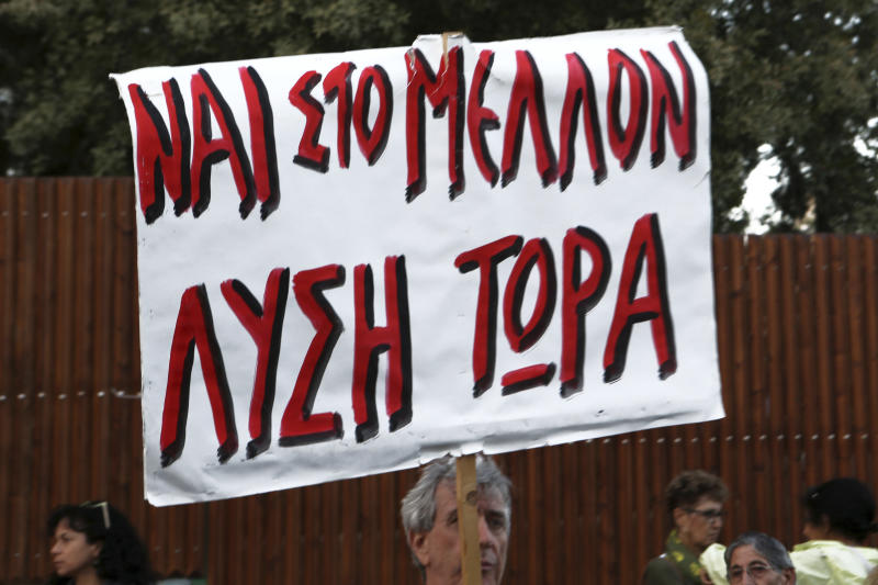 "A protestor holds a banner reading in Greek ""Yes in the future, Solution now"" during a protest staged by Greek and Turkish Cypriots outside the presidential palace in the divided capital Nicosia, Cyprus, Thursday, Oct. 25, 2018. President Nicos Anastasiades, who leads the country's internationally recognized government, and the leader of the breakaway Turkish Cypriots, Mustafa Akinci, are being hosted for a meeting by Elizabeth Spehar, the head of the U.N.'s peacekeeping force in Cyprus, on Oct. 26, 2018. (AP Photo/Petros Karadjias)"