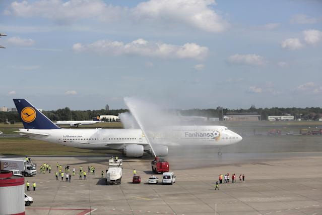 """The plane with the players of German national soccer team arrives at Tegel airport in Berlin Tuesday, July 15, 2014. Germany's World Cup-winning team has returned home from Brazil to celebrate the country's fourth title with huge crowds of fans. The team's Boeing 747 touched down at Berlin's Tegel airport midmorning Tuesday after flying a lap of honor over the """"fan mile"""" in front of the landmark Brandenburg Gate. Words on plane read: Winner Plane and instead of Lufthansa, Fanhansa. (AP Photo/Markus Schreiber)"""