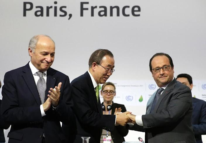 French President Francois Hollande (R) shakes hands with UN secretary general Ban Ki-moon next to French Foreign Minister and COP21 president Laurent Fabius in the final session of the COP21 climate change conference in Paris on December 12, 2015 (AFP Photo/Philippe Wojazer)