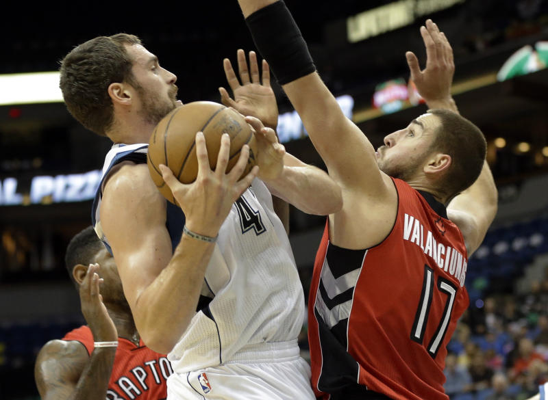 Minnesota Timberwolves' Kevin Love, left, rears back as Toronto Raptors' Jonas Valanciunas, of Lithuania, defends in the first quarter of an NBA preseason basketball game on Saturday, Oct. 12, 2013, in Minneapolis. (AP Photo/Jim Mone)
