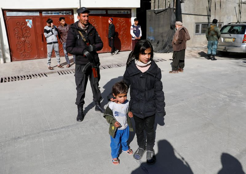 Children watch as body of female judge shot dead by gunmen is carried by relatives in Kabul