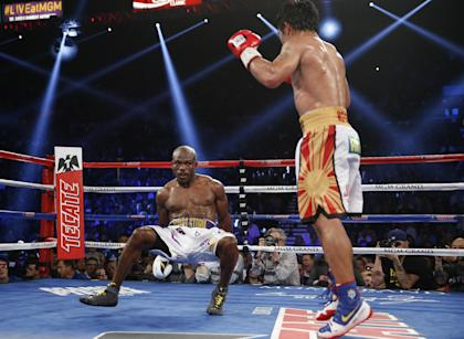 Timothy Bradley falls to the mat after getting hit by Manny Pacquiao. (AP)