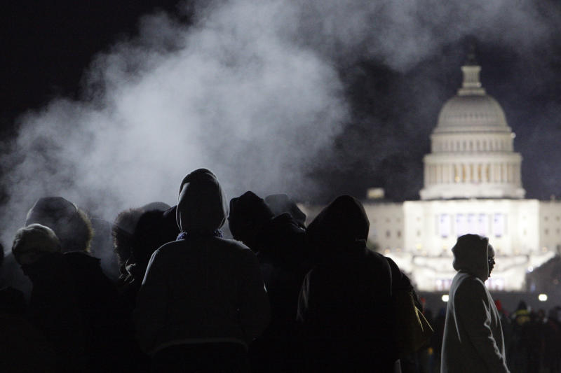 FILE - This Jan. 20, 2009 file photo shows people keeping warm near a steam vent on the National Mall in Washington prior to the start of then-President-elect Barack Obama's inauguration. It will be the first up or down fact check of a Barack Obama campaign pledge for his second term:  Promised warmer Inauguration Day weather.  Will he _ or Mother Nature _ deliver?  It's looking like an uncomfortably close call _ the emphasis on the word uncomfortable for people who will be outside on what's predicted to be a downright chilly day.  (AP Photo/Matt Rourke, File)