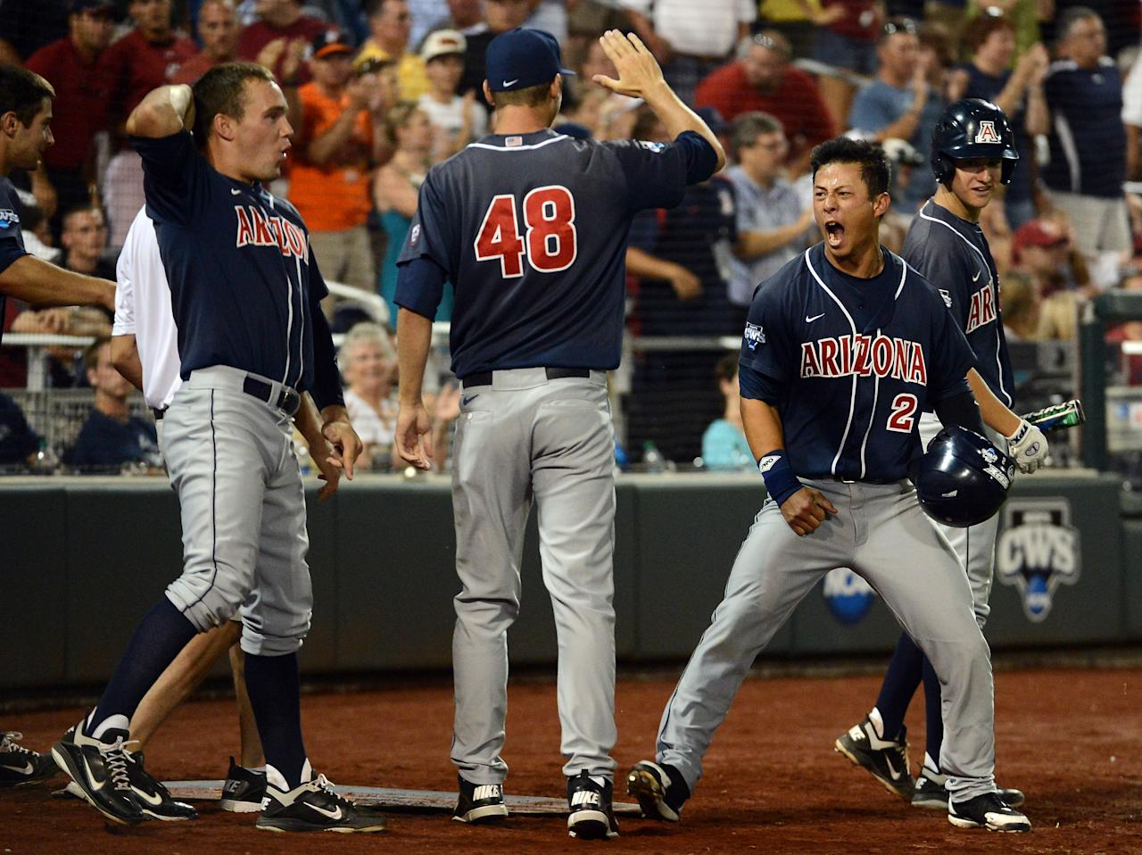 OMAHA, NE - JUNE 25:  Robert Refsnyder #2 of the Arizona Wildcats celebrates his run for a 2-1 lead over the South Carolina Gamecocks with Konner Wade #48 and Johnny Field #1 in the ninth inning during game 2 of the College World Series at TD Ameritrade Field on June 25, 2012 in Omaha, Nebraska.  (Photo by Harry How/Getty Images)