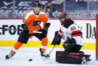 New Jersey Devils' Scott Wedgewood, right, blocks a shot as Philadelphia Flyers' Wade Allison looks for the rebound during the second period of an NHL hockey game, Monday, May 10, 2021, in Philadelphia. (AP Photo/Matt Slocum)
