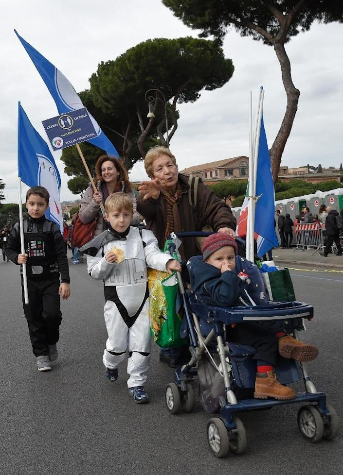 A family walks near the Circus Maximus arena as thousands of demonstrators take part in the Family Day rally in Rome, on January 30, 2016 (AFP Photo/Andreas Solaro)
