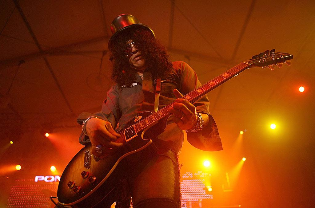 """Slash jams with Velvet Revolver during a performance at 944 Magazine's Super Village, which offered four days and nights of entertainment along the Scottsdale Waterfront leading up to gameday. Shea Walsh/<a href=""""http://www.wireimage.com"""" target=""""new"""">WireImage.com</a> - February 2, 2008"""