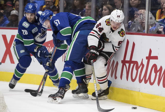 Vancouver Canucks' Tyler Myers (57) checks Chicago Blackhawks' David Kampf (64), of the Czech Republic, during the first period of an NHL hockey game Wednesday, Feb. 12, 2020, in Vancouver, British Columbia. (Darryl Dyck/The Canadian Press via AP)