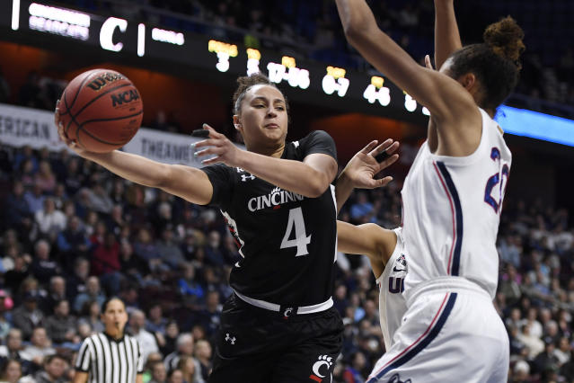 Cincinnati's Angel Rizor (4) passes the ball around Connecticut's Olivia Nelson-Ododa during the second half of an NCAA college basketball game in the American Athletic Conference tournament finals at Mohegan Sun Arena, Monday, March 9, 2020, in Uncasville, Conn. (AP Photo/Jessica Hill)