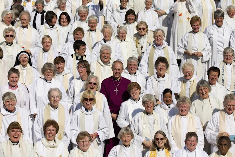 Archbishop of Canterbury Justin Welby (C) poses for pictures with women priests on the steps of St Paul's Cathedral in London, on May 3, 2014, to mark the twentieth anniversary of women becoming ordained priests in the Church of England