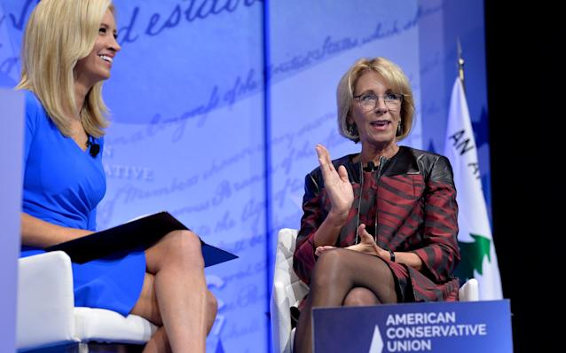 In this file photo Education Secretary Betsy DeVos (R) makes remarks as moderator Kayleigh McEnany (L) listens during a discussion at the Conservative Political Action Conference (CPAC) at National Harbor, Maryland, February 23, 2017.