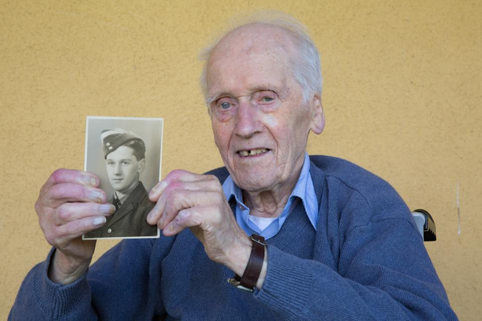 Jim Marshall holds a picture of himself as a young airman (Robert Perry/PA)
