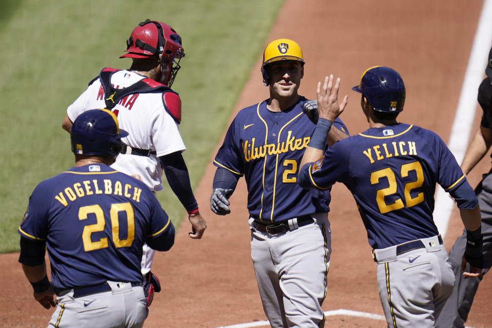 Milwaukee Brewers' Travis Shaw (21) is congratulated by teammates Daniel Vogelbach (20) and Christian Yelich (22) after hitting a three-run home run as St. Louis Cardinals catcher Yadier Molina stands at the plate during the second inning of a baseball game Sunday, April 11, 2021, in St. Louis. (AP Photo/Jeff Roberson)