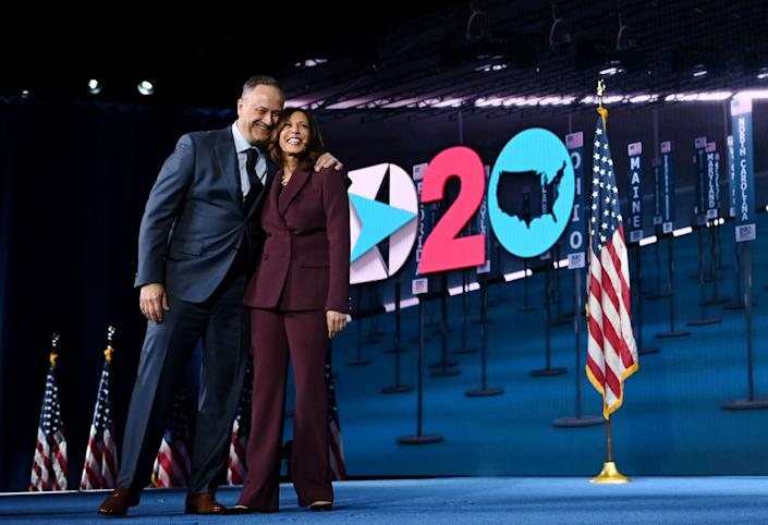Democratic vice presidential nominee Kamala Harris and her husband Douglas Emhoff stand on stage at the end of the third day of the Democratic National Convention.