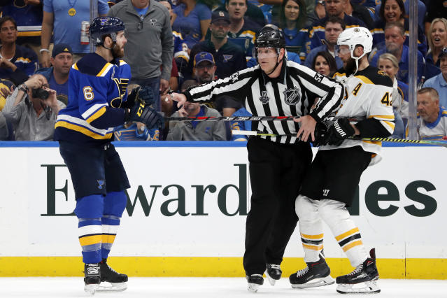 Linesman Greg Devorski (54) separates St. Louis Blues defenseman Joel Edmundson (6) and Boston Bruins right wing David Backes (42) during the second period of Game 3 of the NHL hockey Stanley Cup Final Saturday, June 1, 2019, in St. Louis. (AP Photo/Jeff Roberson)