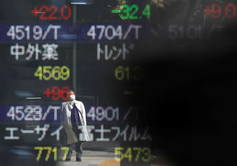 FILE PHOTO: A man wearing a protective face mask is reflected on a stock quotation board outside a brokerage, amid the coronavirus disease (COVID-19) outbreak, in Tokyo
