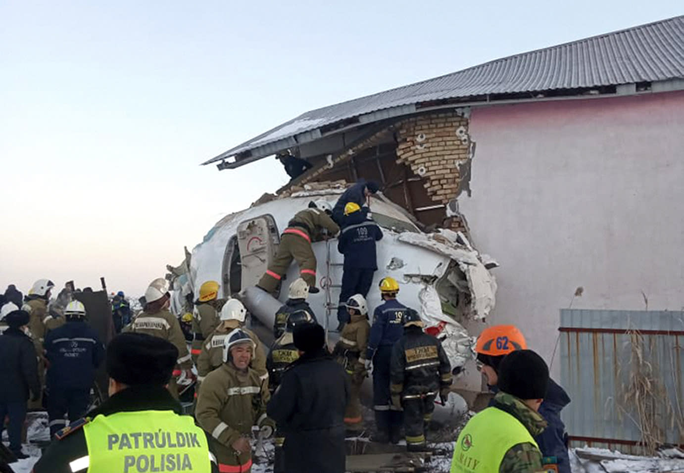 In this photo provided by the Emergency Situations Ministry of the Republic of Kazakhstan, police and rescuers work on the side of a plane crashed near Almaty International Airport, outside Almaty, Kazakhstan, Friday, Dec. 27, 2019. Almaty International Airport said a Bek Air plane crashed Friday in Kazakhstan shortly after takeoff causing numerous deaths. (Emergency Situations Ministry of the Republic of Kazakhstan via AP)