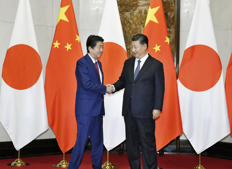 Japanese Prime Minister Shinzo Abe, left, shakes hands with Chinese President Xi Jinping before a meeting at the Diaoyutai State Guesthouse in Beijing Friday, Oct. 26, 2018. (Kyodo News via AP)