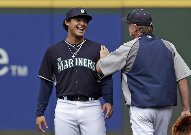 Seattle Mariners' Alex Jackson, left, a newly-signed draft pick, talks with pitching coach Rick Waits before a baseball game Monday, June 23, 2014, in Seattle. Jackson was the team's first-round pick from the amateur draft. He took part in batting practice with the team Monday before their series opener against Boston. Jackson, from San Diego, was regarded as the best high school position player available in the draft. (AP Photo/Elaine Thompson)