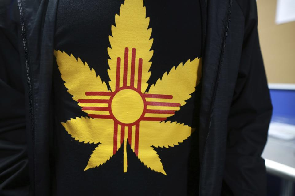 A store worker poses for a photo with his shirt at the Ultra Health medical cannabis dispensary on Tuesday, June 29, 2021, in Santa Fe, New Mexico. Cannabis was legalized for recreational users in New Mexico this year. Residents with medical cards no longer have to pay tax on purchases and can now grow up to six plants. (AP Photo/Cedar Attanasio)