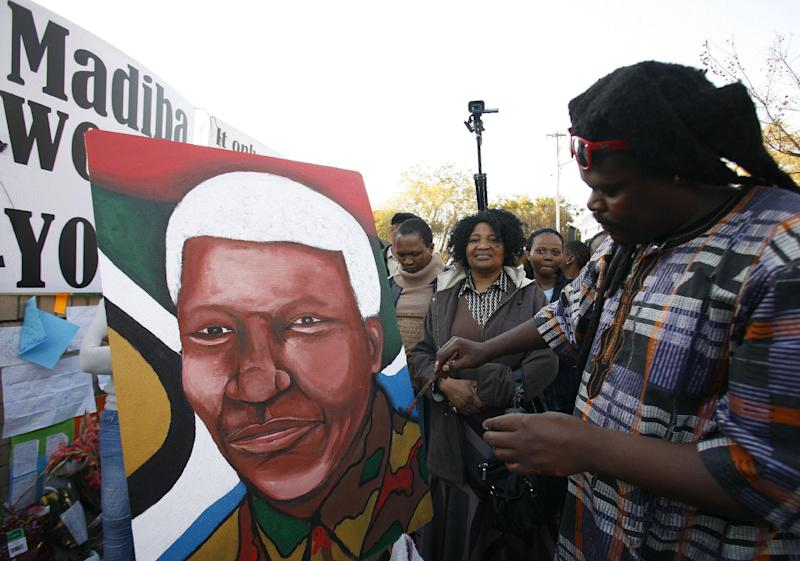 Lebani Sirinje, a Zimbabwean artist paints a portrait of former South African President Nelson Mandela, outside the Mediclinic Heart Hospital where is being treated in Pretoria, South Africa Wednesday, June 26, 2013. South Africa's president Jacob Zuma on Tuesday urged his compatriots to show their appreciation for Nelson Mandela, who is in critical condition in a hospital, by marking his 95th birthday next month with acts of goodness that honor the legacy of the anti-apartheid leader. (AP Photo/Themba Hadebe)