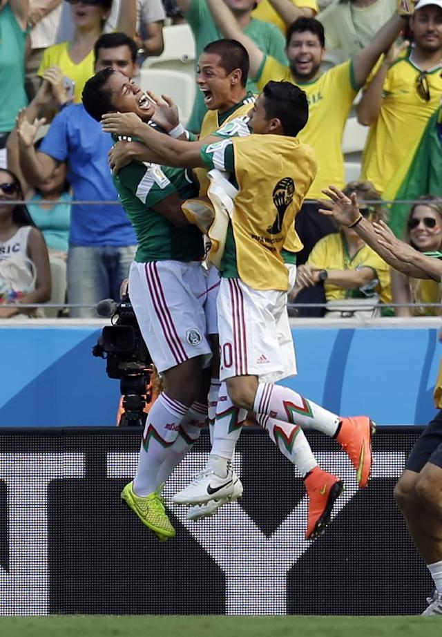 Mexico's Giovani dos Santos, left, celebrates after scoring the opening goal during the World Cup round of 16 soccer match between the Netherlands and Mexico at the Arena Castelao in Fortaleza, Brazil, Sunday, June 29, 2014. (AP Photo/Natacha Pisarenko)