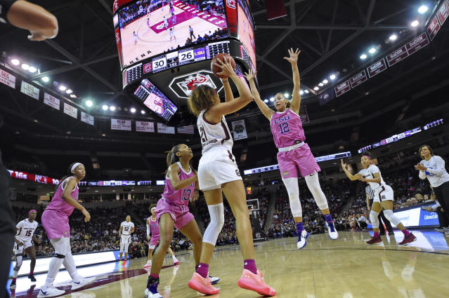 South Carolina's Mikiah Herbert Harrigan (21) passes while defended by LSU's Jaelyn Richard-Harris (13) and Mercedes Brooks during the first half of an NCAA college basketball game Thursday, Feb. 20, 2020, in Columbia, S.C. (AP Photo/Richard Shiro)