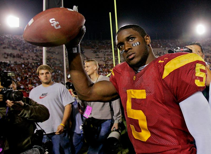 FILE - In this Nov. 19, 2005, file photo, Southern California tail back Reggie Bush walks off the field holding the game ball after the Trojans defeated Fresno State, 50-42, at the Los Angeles Coliseum. USC set a record by going 33 straight polls as No. 1 from 2003-05. The Trojans weren't just the best team in college football, they were also arguably the coolest, with the charismatic, laid-back Carroll leading stars like quarterback Matt Leinart and running back Reggie Bush to victory after victory. (AP Photo/Kevork Djansezian, File)