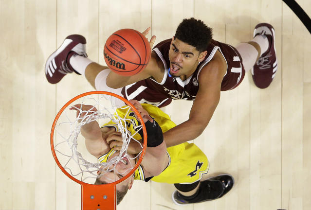 Texas A&M center Tyler Davis, top, shoots against Michigan forward Moritz Wagner during the first half of an NCAA men's college basketball tournament regional semifinal Thursday, March 22, 2018, in Los Angeles. (AP Photo/Alex Gallardo)