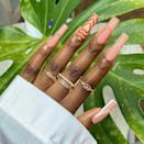 """Brooklyn-based nail artist <a href=""""https://www.instagram.com/enchantedclaws/"""" rel=""""nofollow noopener"""" target=""""_blank"""" data-ylk=""""slk:Zey"""" class=""""link rapid-noclick-resp"""">Zey</a> is responsible for artfully painting this nude French manicure. These C-curve tips are completely hollow and outlined simply in a tan, white, or brown color. The ring finger has Powerpuff Girls-inspired hearts in a series of similar shades."""