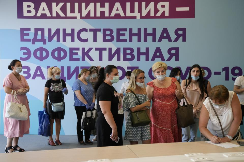 """FILE - In this Thursday July 8, 2021 file photo, people, some of them foreigners working in Russia, arrive at a vaccination center with the slogan """"vaccination is the only effective protection against coronavirus"""" in the background in the Luzhniki Olympic Complex in Moscow, Russia. Faced with worrying surges of coronavirus infections driven by the more transmissible delta variant, European nations have been scrambling to ramp up vaccination drives, using a mixture of stick-and-carrot measures to persuade the reluctant to get their shots. (AP Photo/Alexander Zemlianichenko, File)"""
