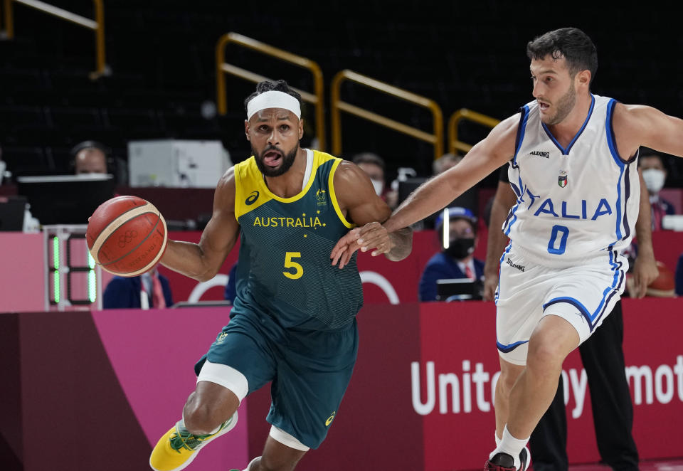 Australia's Patty Mills (5) drives around Italy's Marco Spissu (0) during a men's basketball preliminary round game at the 2020 Summer Olympics, Wednesday, July 28, 2021, in Saitama, Japan. (AP Photo/Eric Gay)