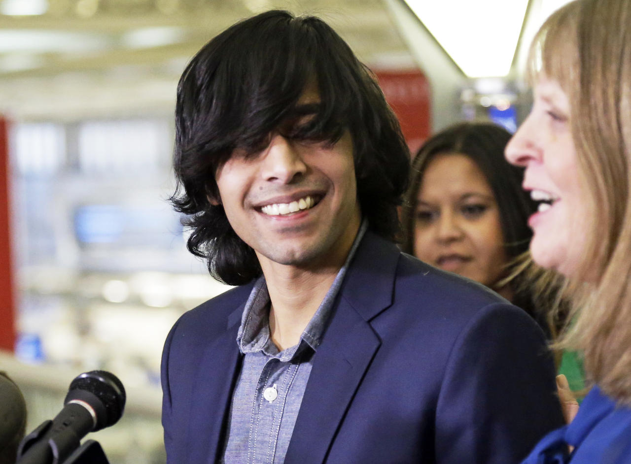 Shezanne Cassim, left, laughs after his attorney, Susan Burns answered a reporter's question after he arrived at the Minneapolis-St. Paul International Airport in Minneapolis on Thursday, Jan. 9, 2014. Cassim had been held in a maximum security prison since June 2013 in the United Arab Emirates for a parody video that was posted online. (AP Photo/Jim Mone)
