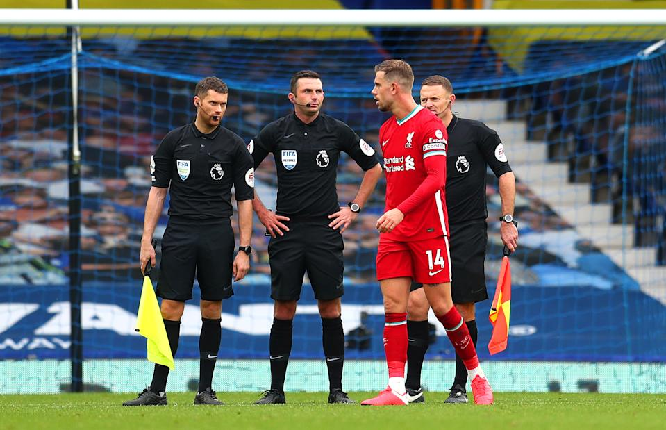 Liverpool captain Jordan Henderson speaks with officials after his apparent game-winning goal was ruled out. (Catherine Ivill/Getty Images)