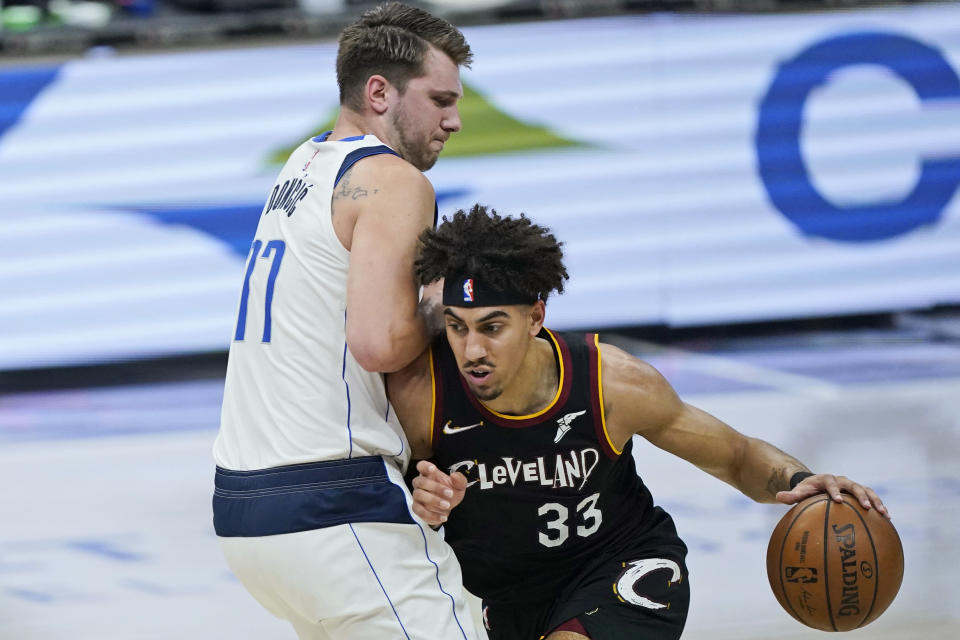 Dallas Mavericks' Willie Cauley-Stein (33) drives against Dallas Mavericks' Luka Doncic (77) during the first half of an NBA basketball game Sunday, May 9, 2021, in Cleveland. (AP Photo/Tony Dejak)