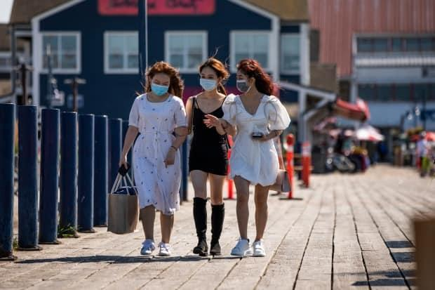Three women walk along the boardwalk in Steveston Harbour, about 20 km south of Vancouver.
