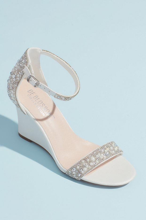 """<p>davidsbridal.com</p><p><strong>$69.95</strong></p><p><a href=""""https://go.redirectingat.com?id=74968X1596630&url=https%3A%2F%2Fwww.davidsbridal.com%2FProduct_crystal-and-jewel-embellished-wedge-sandals-etta_comfort-shoes&sref=https%3A%2F%2Fwww.thepioneerwoman.com%2Ffashion-style%2Fg36122557%2Fcomfortable-wedding-shoes%2F"""" rel=""""nofollow noopener"""" target=""""_blank"""" data-ylk=""""slk:Shop Now"""" class=""""link rapid-noclick-resp"""">Shop Now</a></p><p>Any bride who wants to avoid a towering heel while still displaying some glitz and glam will love these wedge sandals. The straps and back of the heel are decked out in jewels, while the low wedge provides plenty of comfort.</p>"""