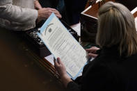 FILE - In this Jan. 7, 2021, file photo the signed certificate of Electoral College votes from Pennsylvania is held by a staff member during a joint session of the House and Senate to confirm the Electoral College votes cast in November's election, at the Capitol, in Washington. (AP Photo/Andrew Harnik, File)