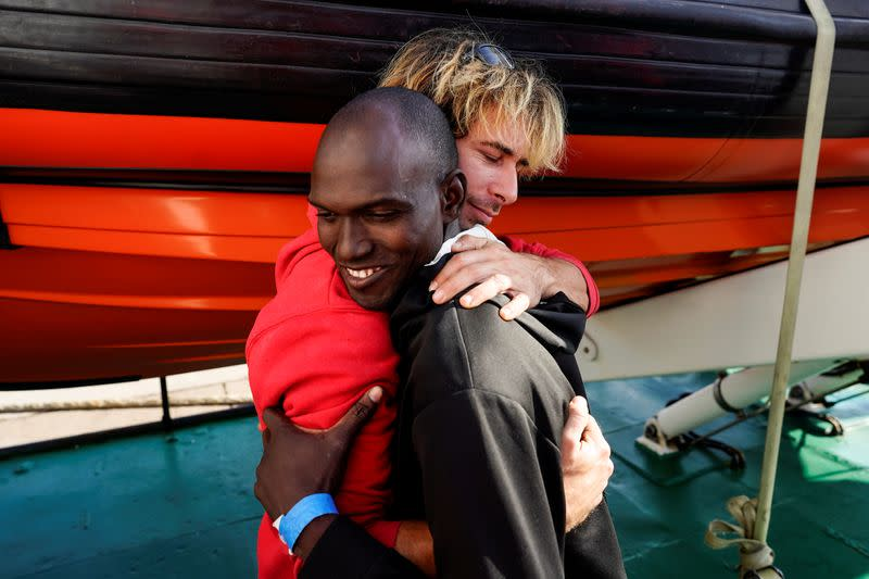 FILE PHOTO: A crew member embraces a migrant on board of NGO Proactiva Open Arms rescue boat, at the Port of Taranto