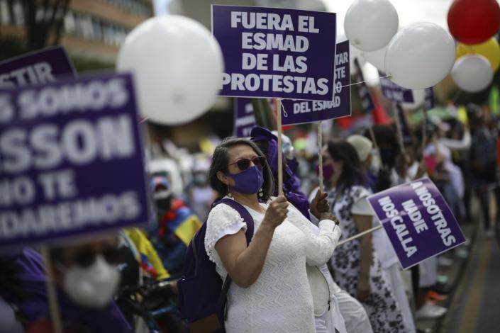 A protester holds a sign demanding police stay out of protests during an anti-government march in Bogota, Colombia, Wednesday, May 19, 2021. Colombians have taken to the streets for weeks across the country after the government proposed tax increases on public services, fuel, wages and pension. (AP Photo/Ivan Valencia)