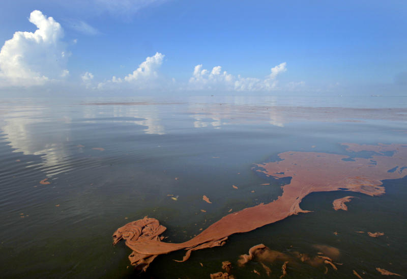 FILE - Oil from the Deepwater Horizon spill floats on the water as the sky is reflected in sheen on Barataria Bay, off the coast of Louisiana, in this June, 7, 2010 file photo. A high-stakes trial to assign blame and help figure out exactly how much more BP and other companies should pay for the spill began Monday, Feb. 25, 2013. (AP Photo/Charlie Riedel, File)