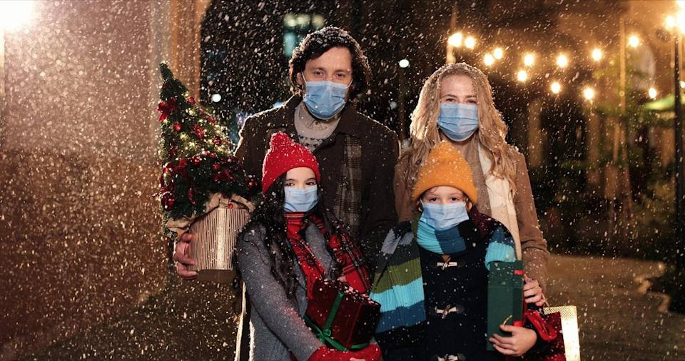 man, woman, and children wearings masks outside in the snow and holding Christmas gifts