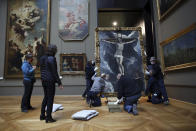 Workers handle a painting called 'Christ on the Cross Adored by Two Donors' by Spanish painter El Greco, as it returns from an exhibition at the Chicago Institute, in the Louvre museum, in Paris, Tuesday, Feb. 9, 2021. The forced closure has also granted museum officials a golden opportunity to carry out long-overdue refurbishments that were simply not possible with nearly 10 million visitors a year. (AP Photo/Thibault Camus)