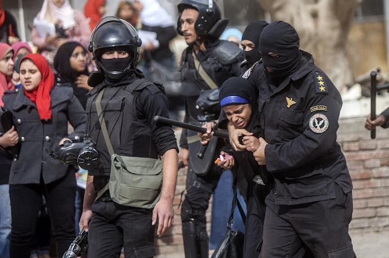 An Egyptian riot policeman detains a female student of al-Azhar University during a protest inside their campus in Cairo on December 30, 2013 (AFP Photo/Mahmoud Khaled)